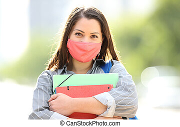 Happy student with mask posing in the street