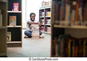 Happy Student With Stacked Books Sitting In Library