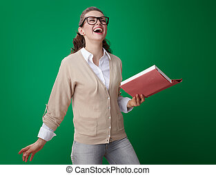 happy student woman with book isolated on green background