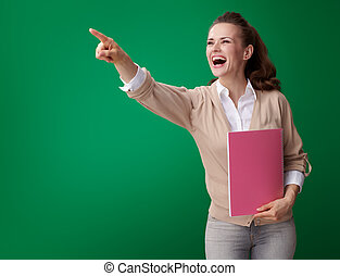 happy student woman with pink notebook pointing at something