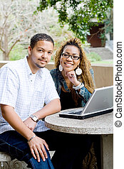 happy students - happy college students smiling and using...