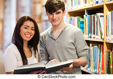 Happy students holding a book in a library