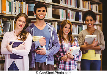 Happy students holding books in row in library
