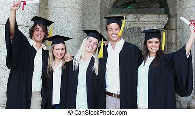 Happy students hugging while holding diplomas