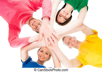 Happy students in colorful clothing standing together holding hands.