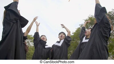 happy students in graduation gowns holding diplomas on ...