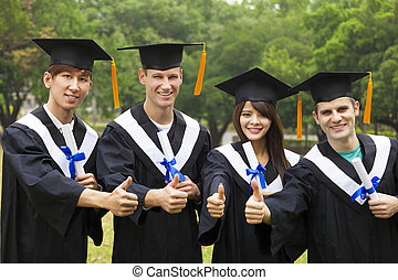 happy students in graduation gowns showing diplomas with thumbs