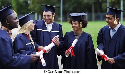 happy students in mortar boards with diplomas - education, ...