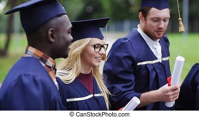 happy students in mortar boards with diplomas