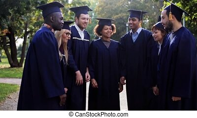 happy students in mortar boards with hands on top