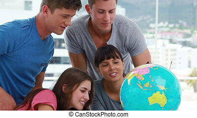 Happy students looking at a globe