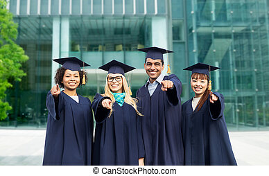 happy students or bachelors pointing finger at you
