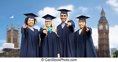 happy students or bachelors pointing finger at you -...