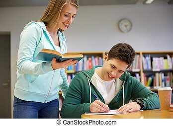 happy students preparing to exams in library - people,...