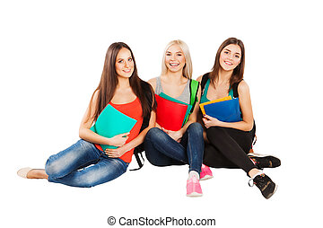 Happy students sitting together with fun, while smiling and looking at camera isolated on white background.