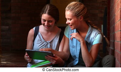 Happy students sitting using tablet