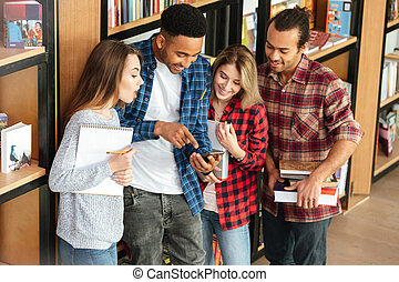 Happy students standing in library using mobile phone