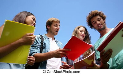 Happy students standing outside chatting on college campus
