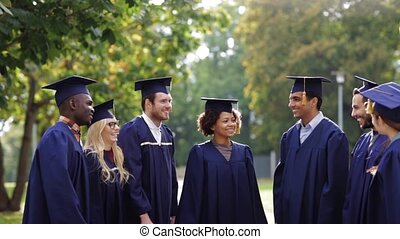 happy students throwing mortar boards up - education,...