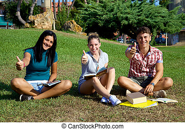 Good looking teenager smiling and having fun studying in park
