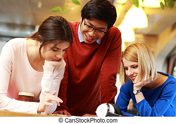 Happy students using tablet computer together