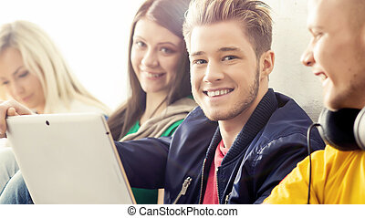 Happy students with a tablet computer