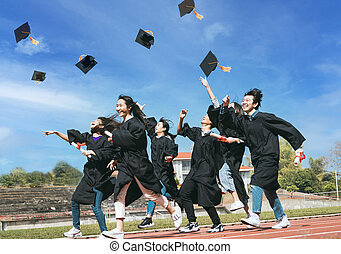 Happy Students with congratulations throwing graduation hats in the air for celebrating