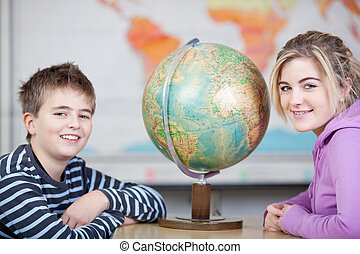 Happy Students With Globe At Desk