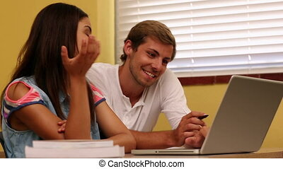 Happy students working together on laptop