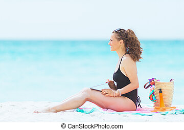 happy stylish 40 year old woman on white beach with laptop
