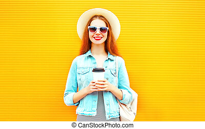 Happy stylish girl with coffee cup on a orange background