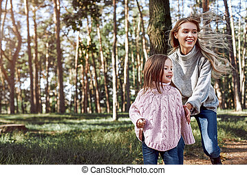 Happy, stylish little curly girl is walking with her beautiful mother in forest
