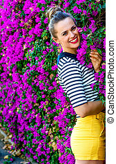 happy stylish woman against colorful magenta flowers bed -...