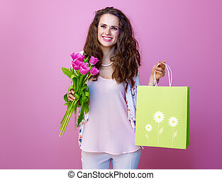 happy stylish woman with bouquet of tulips showing shopping bag