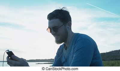 Happy stylish young man writes sms near the sea. In the sky the airplane is flying leaving a trail. A handsome man with headphones and round glasses.