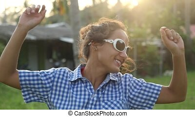 Happy stylish young woman in sunglasses dancing in the sun between tropical palm trees enjoying his vacation at Sunset time. Slow Motion. 1920x1080