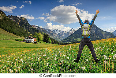 Happy succesful Hiker with Backpack jumping with raised arms on Hawkbit Flower meadow. Snow covered mountains and traditional house. Bavaria, Alps, Oberstdorf, Allgau, Germany.