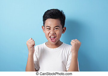 Happy success Asian boy shows winning gesture
