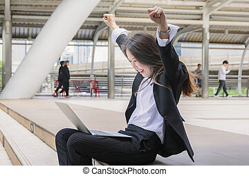 Happy successful business woman with arms up,business outside