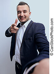 Happy successful businessman pointing on copy space
