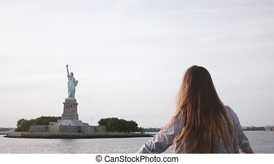 Happy successful businesswoman with hair blowing in the wind enjoying epic Statue of Liberty view on a boat slow motion.