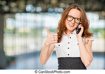 Happy successful businesswoman with phone posing in the office