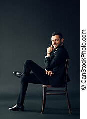 Happy successful man in black suit smiling and looking to camera sitting on the chair
