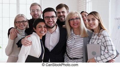 Happy successful multiethnic team looking at camera bonding, business portrait