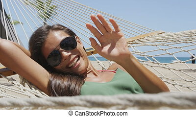 Happy beach girl tanning in aviator sunglasses relaxing in outdoor bed hammock saying hi waving hello at camera smiling happy during summer holidays. Asian woman on tropical destination getaway.