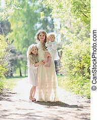 Happy sunny family, mother with her daughters in a warm summer d
