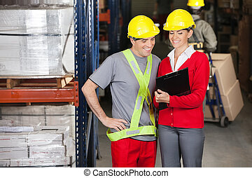 Happy Supervisor Showing Clipboard To Foreman