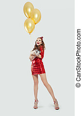 Happy surprised woman in red glitter dress holding little pig and yellow balloons on white background