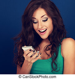 Happy surprising makeup young woman looking on mobile phone with open mouth on blue background. Toned bright closeup portrait