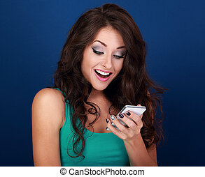 Happy surprising makeup young woman looking on mobile phone with open mouth on blue background